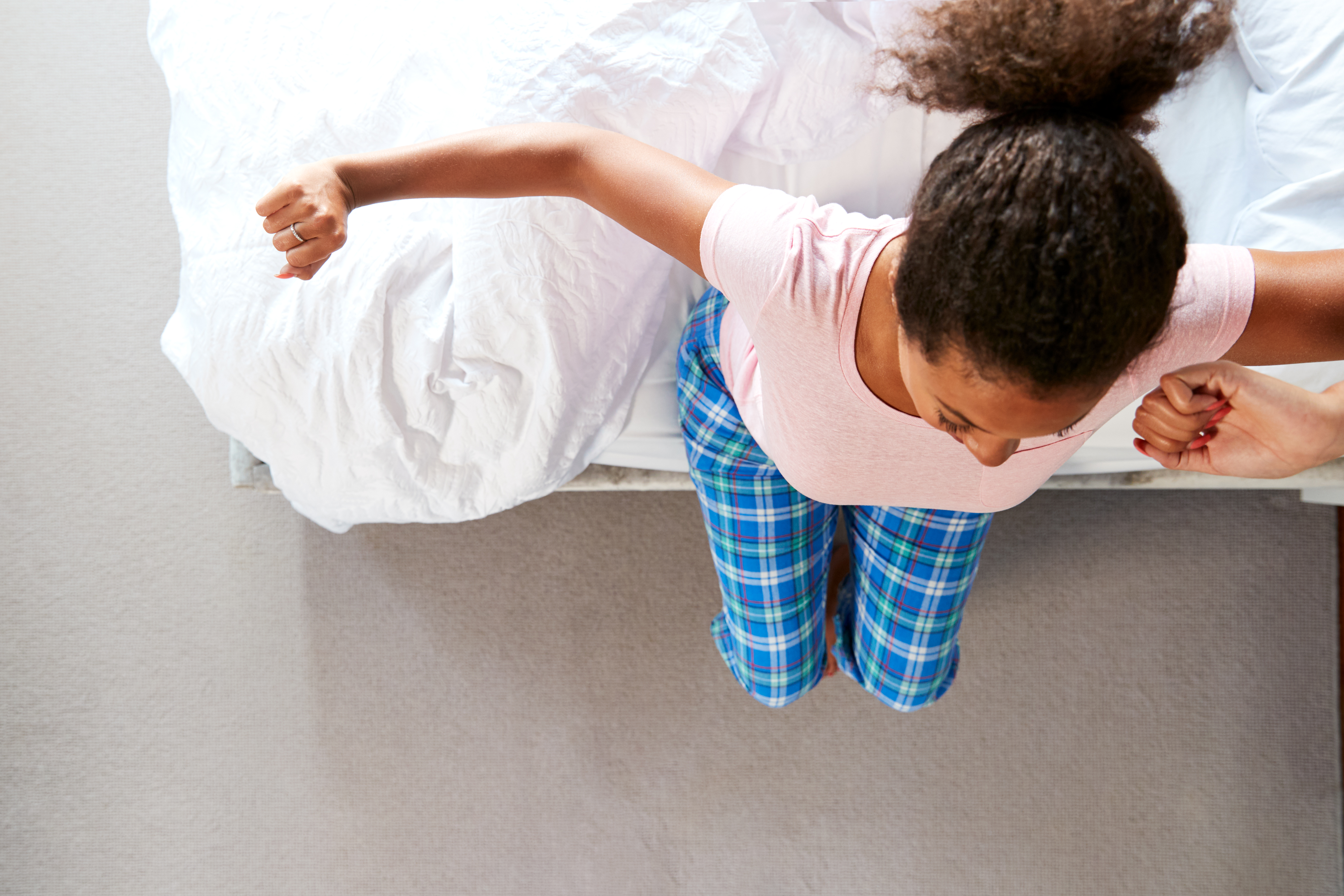 Overhead View Of Woman Wearing Pajamas Stretching As She Gets Out Of Bed At Home @Lunar Sleep Systems